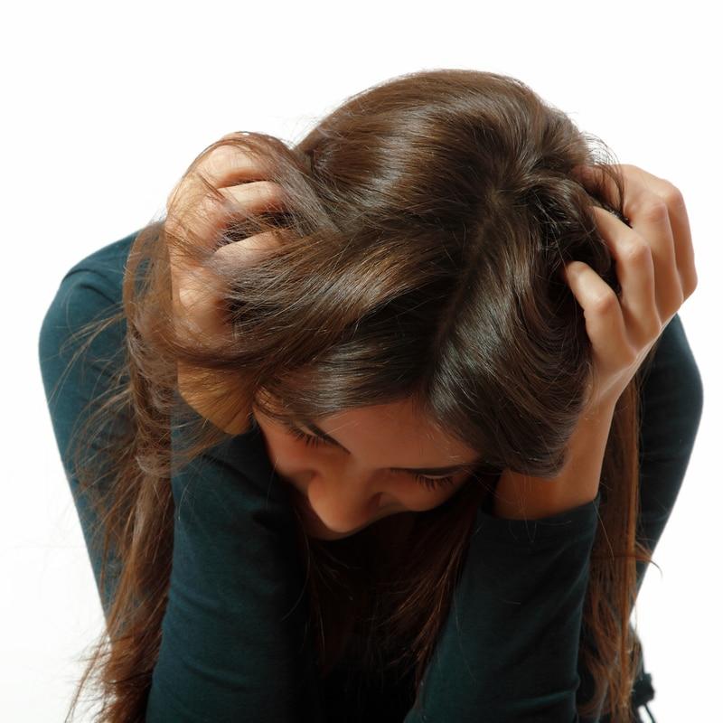 Una joven agarrando su cabello de forma desesperada con la vista al suelo.