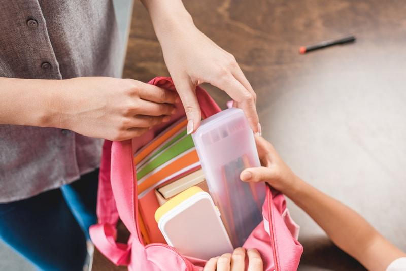 niñDonarán 2,000 mochilas con útiles escolares a estudiantes de Greensboroo llenando su mochilas con lápices
