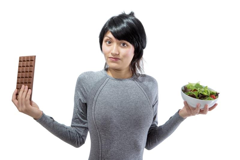 Una mujer con un plato de verduras en una mano y una barra de chocolate en la otra