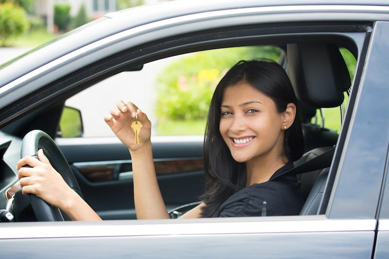 Una joven sonriendo dentro su primer auto.