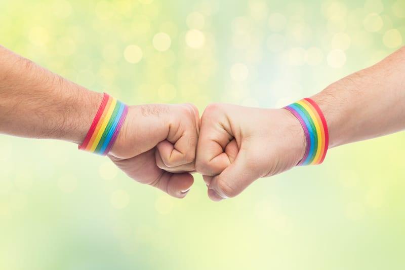 Un niño y su papá choca los puños, con pulsera con la bandera de arco iris.
