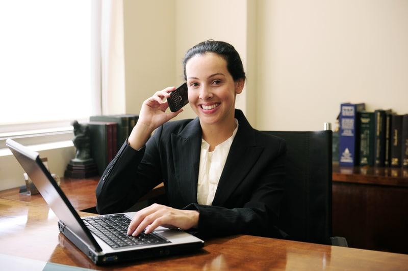 una abogada con un telefono y computadora en mano