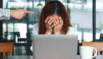 Una mujer llorando siendo acosada por un compañero