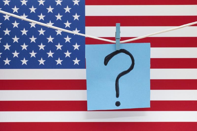 igno de interrogación enfrente de una bandera Estadounidense.