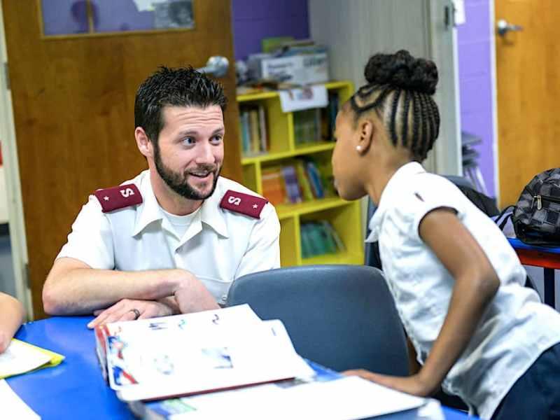 Un miembro del Salvation Army hablando con una niña.