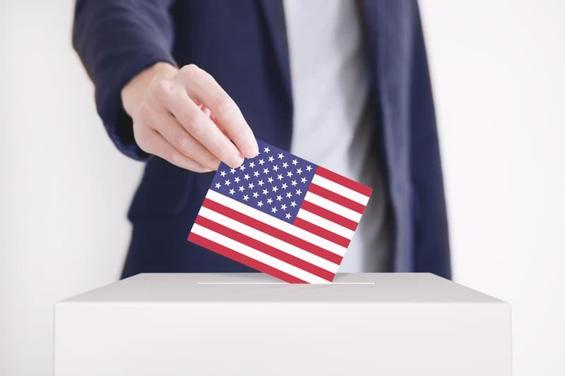 Hombre poniendo una boleta con la bandera de los Estados Unidos en una casilla de votación.