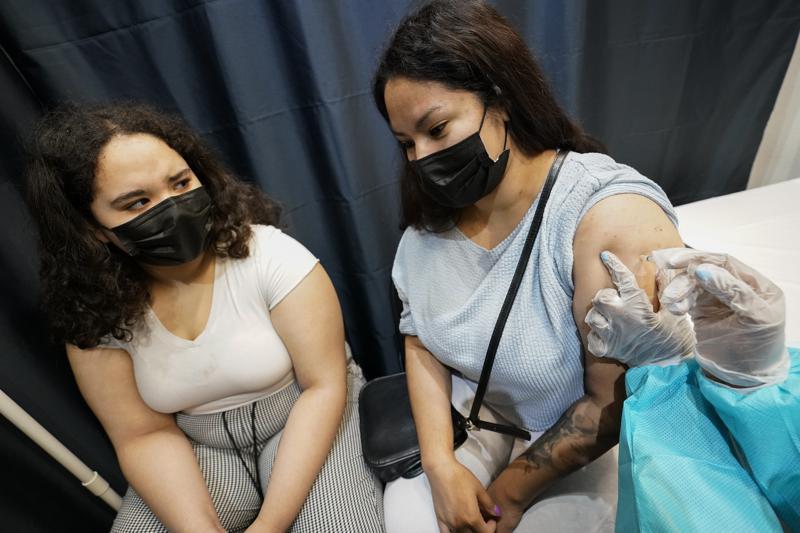 Un trabajador de la salud vacuna a Evelyn Pereira, derecha, de Brooklyn, con la primera dosis de la vacuna Pfizer COVID-19 mientras su hija Soile Reyes, de 12 años, observa el jueves 22 de julio de 2021 en el Museo Americano de Historia Natural en Nueva York. Foto AP / Mary Altaffer