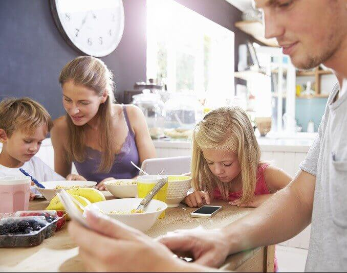 Family Using Digital Devices At Breakfast Table