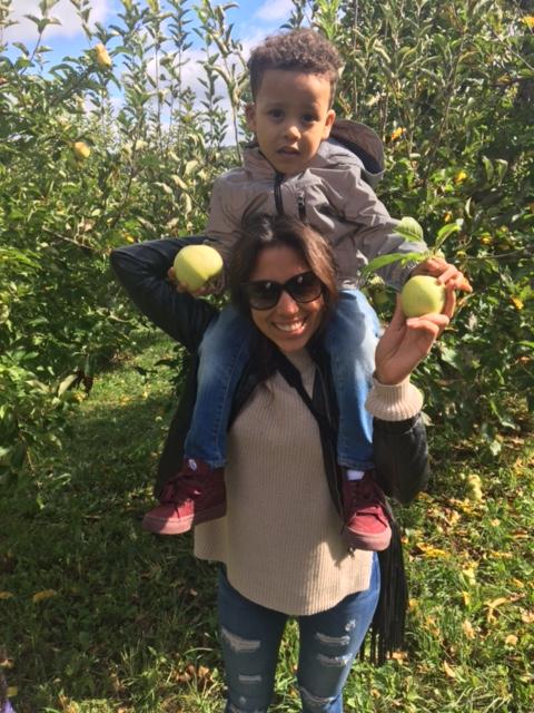 A Lantern staff member helps a child pick apples at Fishkill Farms