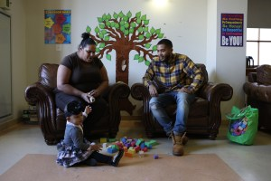 A social worker and tenants meet in one of Lantern Community Services family play areas