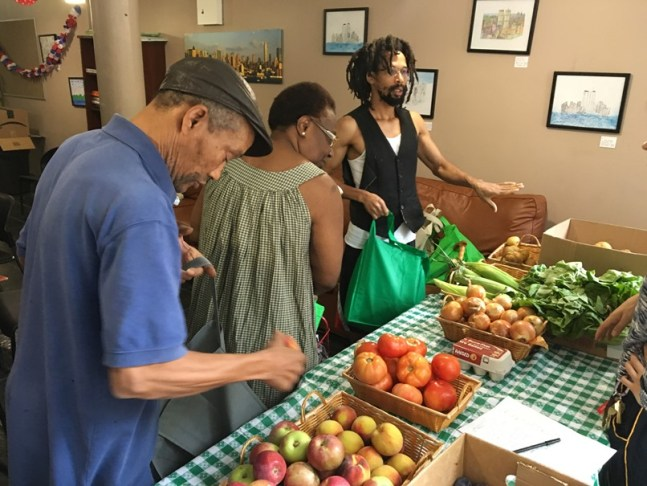 Huntersmoon Hall residents participate in the food box program in the un-renovated community space