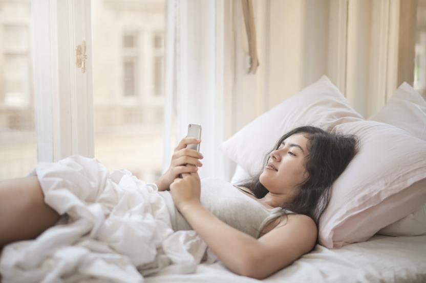 young woman using smartphone in bed 3807633 - 5 malos hábitos que afectan la energía positiva