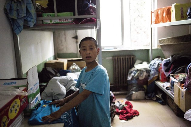 "Jingtao, 14, trying to find cloth for his trip to Beijing in the storage room. His mother passed away due to HIV/AIDs, and he was infected via breast feeding. Jingtao is showing drastic mood change for unknown reason. He went from a talkative, love to sing and perform, happy boy to a quite and stay to himself type within six months. Photo by Ann Wang Children of the Harbor project: This is an on-going project about a school in rural China that only accepts HIV positive children. The school provides a total of 30 students age from 6 to 19, free education, accommodation, food and medication. However, because the geographic location and the nature of the school, the children is isolated from the public. The first generation of the students will be graduating in 2017, and will have to leave this ""safe-heave"" for the first time in their life. This project takes a in-depth look of life inside the school, and documents the growth of each of the children, up until the day they have to officially step out of the bubble."