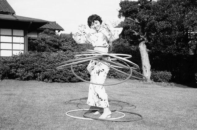 Seorang wanita muda Jepang dalam busana kimono tampak ikut terjangkit demam Hula-Hoop yang saat itu melanda Amerika dan Jepang, dalam foto bertanggal 30 Oktober 1958. (Photo by Mitsunori Chigita/AP Photo via The Atlantic)
