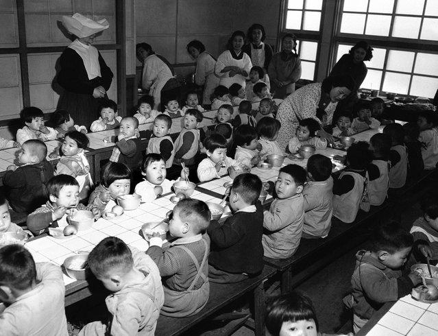 Ruang makan di sebuah panti asuhan di Osaka, Jepang, pada 19 Februari 1951, dimana 160 orang anak yatim piatu diberi makan setiap hari yang dibiayai oleh the Wolfhounds, resimen infanteri ke-27 dari angkatan darat Amerika Serikat. (Photo by Jim Pringle/AP Photo via The Atlantic)