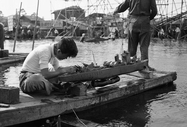 Seorang pekerja studio film mengerjakan salah satu model kapal perang yang digunakan dalam sebuah adegan pertempuran di sebuah film dokumenter Jepang yang menceritakan kisah hari terakhir kapal perang Yamato, 8 Juni 1953. (Photo by Yuichi Ishizaki/AP Photo via The Atlantic)