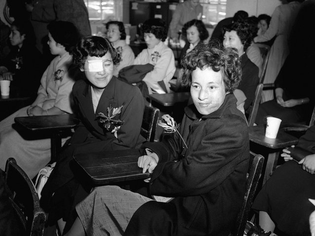 Mitsuko Kuranoto (kiri) dan Emiko Takemoto, adalah korban yang selamat dari bom atom Hiroshima yang terjadi 10 tahun sebelumnya. Dalam kesempatan ini, dia sedang berada di pangkalan Angkatan Udara Mitchel di Long Island, New York, 9 Mei 1955. Dua puluh lima orang gadis Jepang, yang terluka karena bom atom tersebut, terbang sejauh 11000 ke New York dengan harapan keajaiban operasi plastik dapat memberikan mereka wajah yang baru. (Photo by Jacob Harris/AP Photo via The Atlantic)