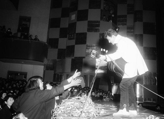"Micky Curtis, seorang penyanyi bergaya mirip Elvis Presley, memainkan gitarnya dan menyanyi, selagi para gadis pemujanya berusaha meraihnya, di Nichigeki Theater di Tokyo pada 18 Februari 1958. Jepang saat itu dilanda demam ""Rock'n Roll"" sehingga musik barat pun merajai tangga lagu Jepang. (Photo by AP Photo via The Atlantic)"