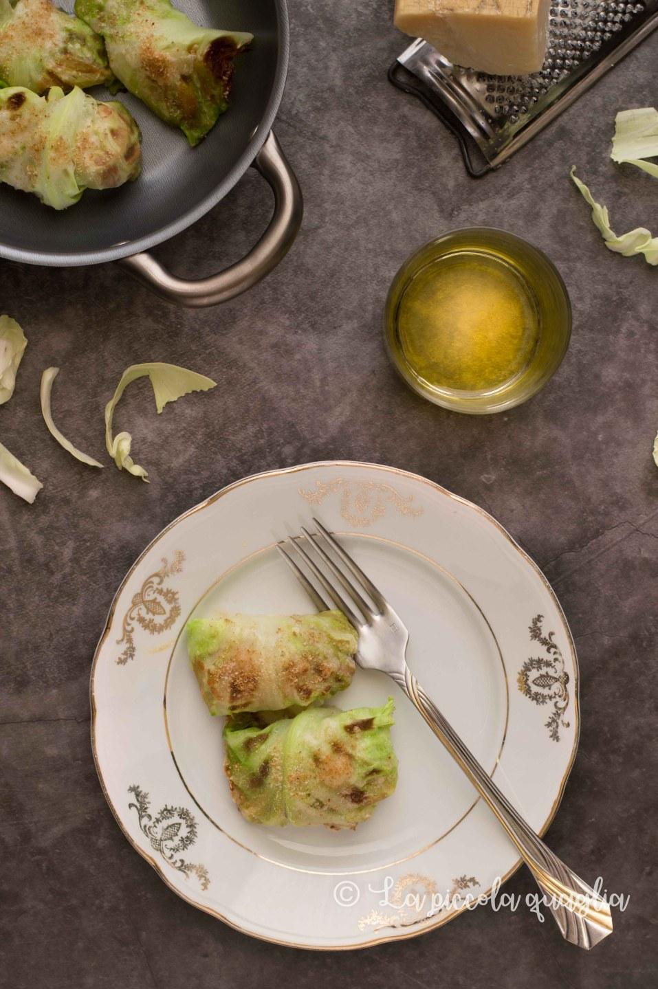 involtini di cavolo verza in un piatto bicchiere di vino bianco