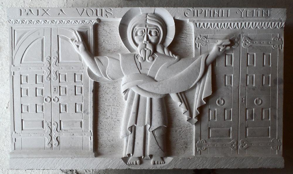 """Bas-relief du Christ apparaissant """"toutes portes closes"""" avec les portes derrière. """"Paix à vous"""" gravé en français et en grec sur le cadre."""