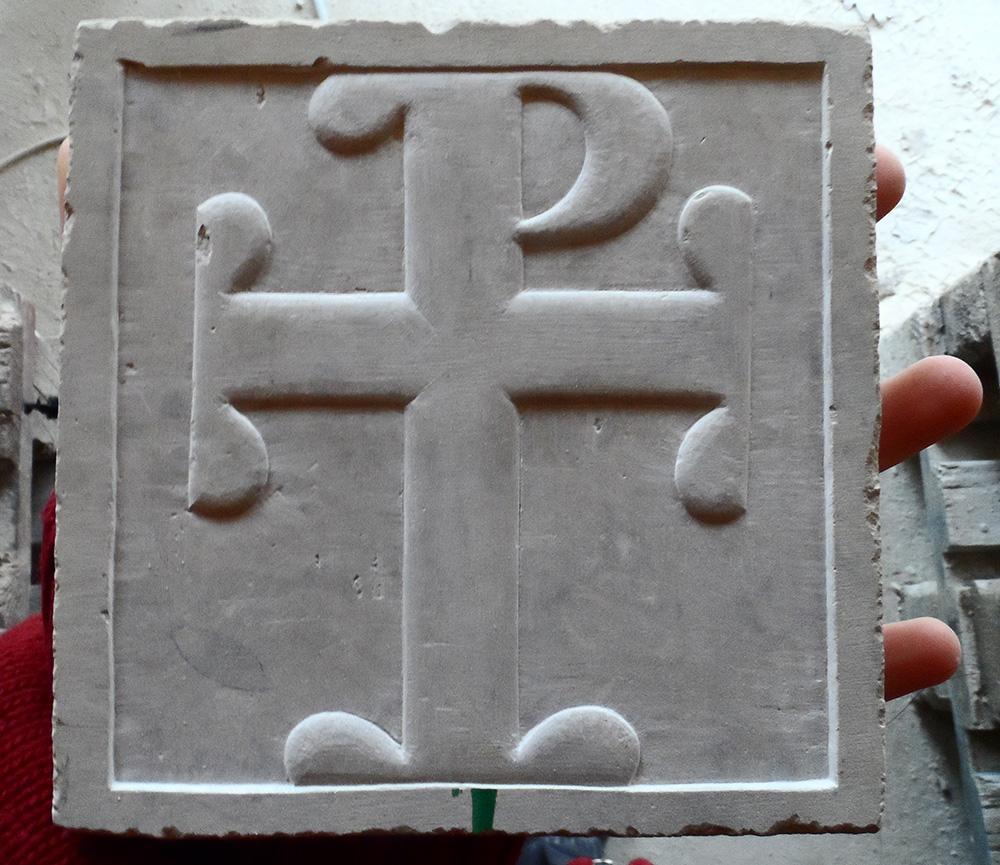 Petite croix en relief sur un carré de tavel jaune