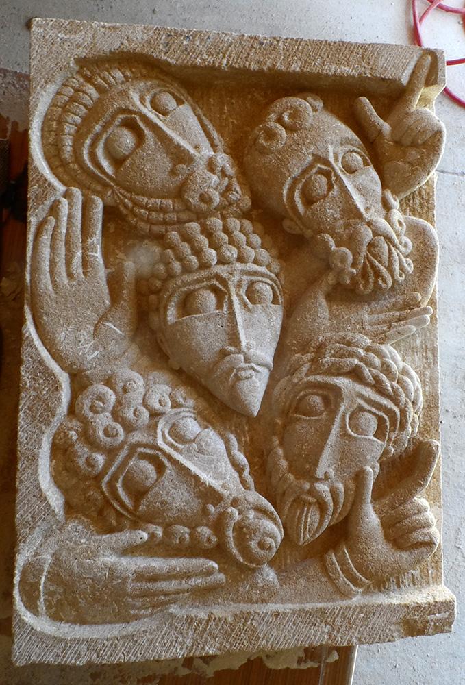 Bas-relief en pierre de dordogne représentant 5 visages et 5 mains entremêlés.