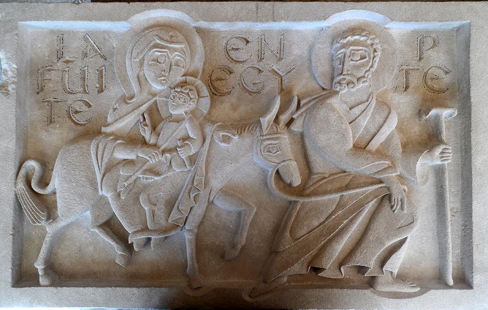 bas-relief en st maximin représentant la scène de la fuite en Egypte. Le nom de la scène est gravé en fond. Joseph marche, Marie et l'enfant Jésus sont sur un âne.