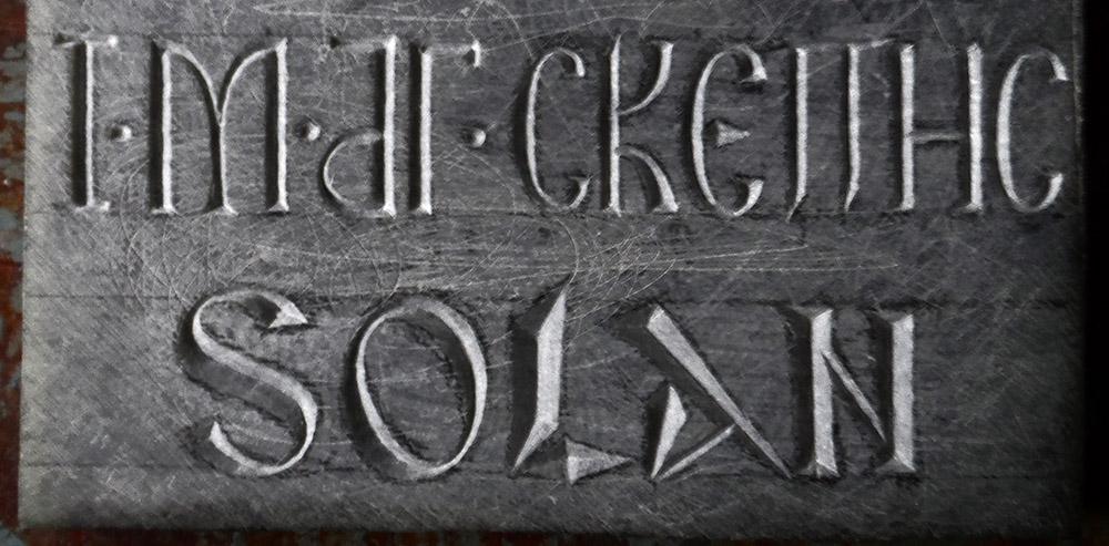 Gravure en caractères grecs (ligne du haut) et latins au dos d'un petit panneau de stéatite.