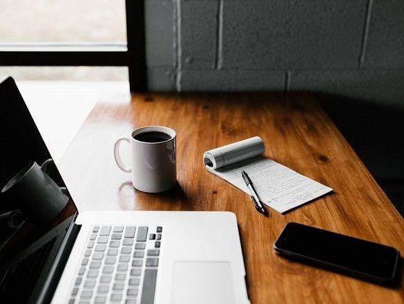 Laptop MacBook Pro taza blanca y cuaderno de notas