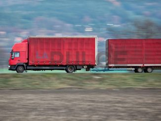 red camion/truck goes fast on a road (panned image - motion blur