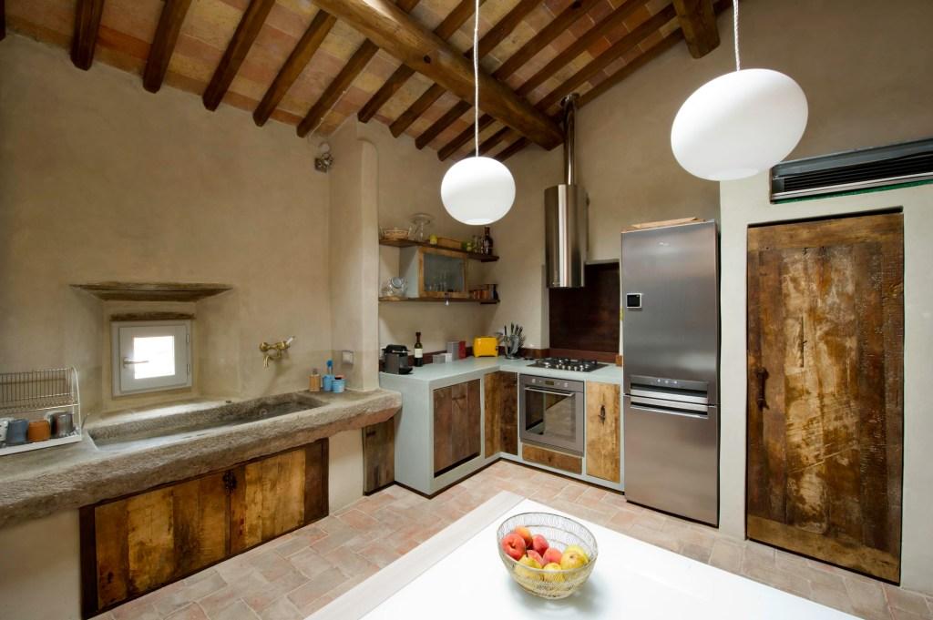 Il legno di un vecchio solaio in castagno può essere rigenerato e diventare il segno distintivo di una cucina artigianale dove la resina grigia si unisce ad un lavabo antico in pietra e a pannelli di ferro ossidato