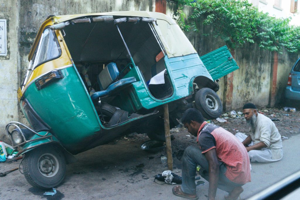 Fixing their Auto Rickshaw on the side of the road.