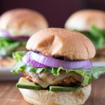 picture of grilled turkey burger sliders from the front with lettuce, red onion, and avocado.