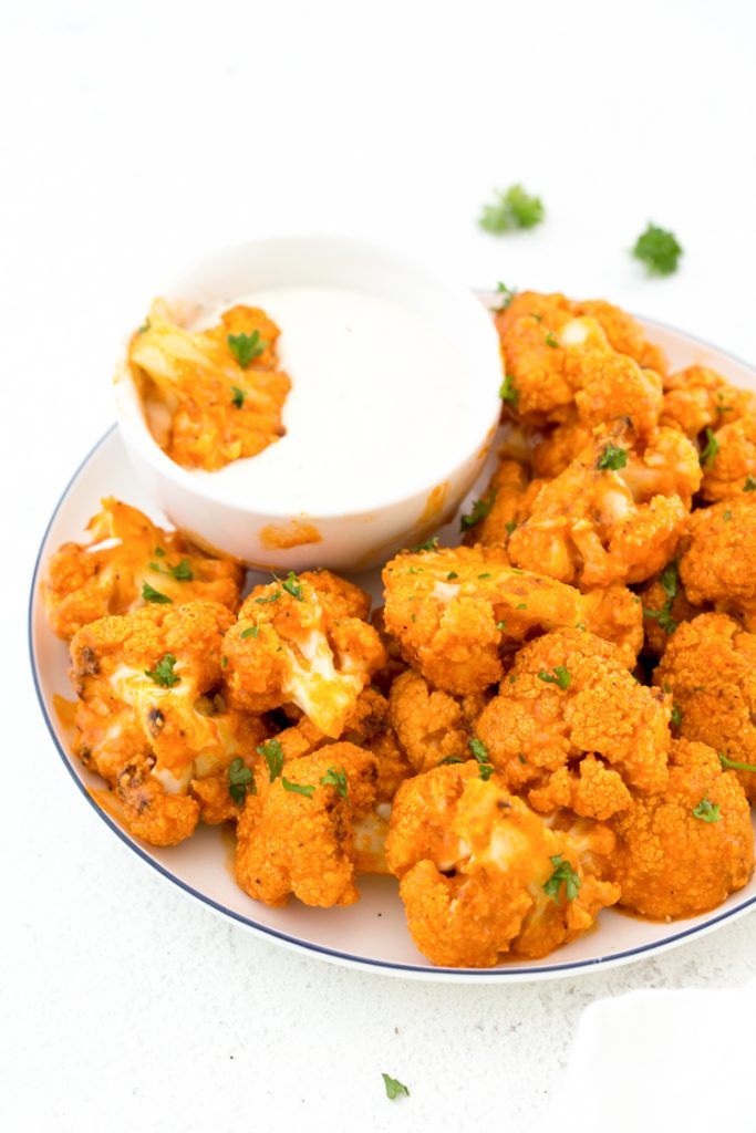 keto buffalo cauliflower on a plate with a side of blue cheese topped with parsley