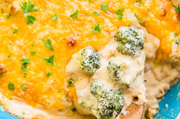 broccoli and cheese casserole in a blue baking dish with a wooden spoon