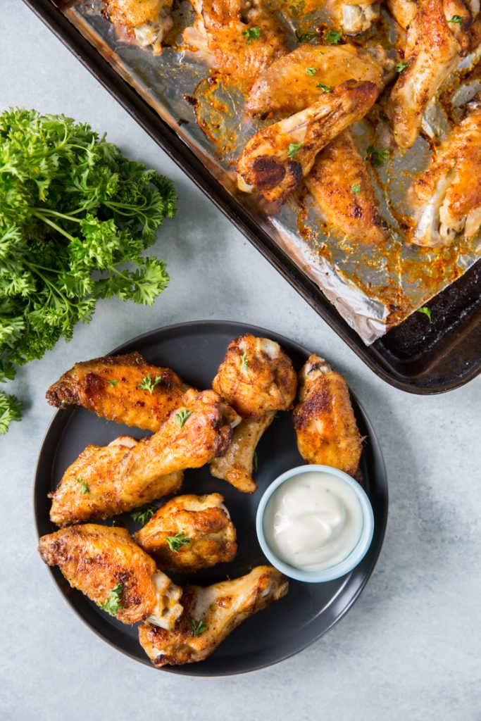 keto chicken wings on a plate with ranch topped with parsley and a bunch of parsley