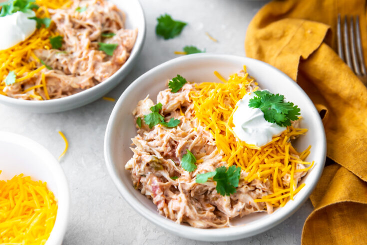creamy Instant Pot salsa chicken in a bowl topped with cheese, sour cream and cilantro