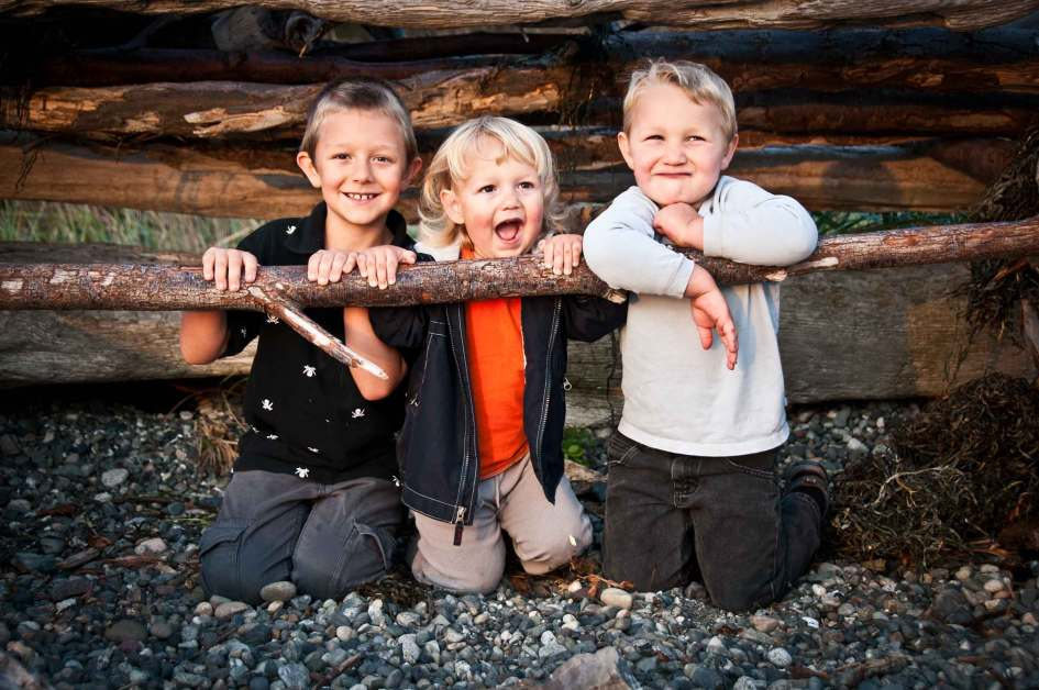 Portrait Of Three Kid Brothers In A Log Fort At The Beach