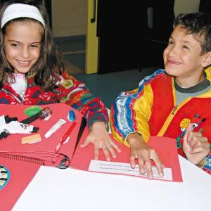 Uma menina e um menino de aproximadamente 8 anos, estão sentados em frente à uma mesa, onde estão os livros do Brincando com as Horas. Ambos tocam uma página do livro e têm no rosto, largo sorriso.