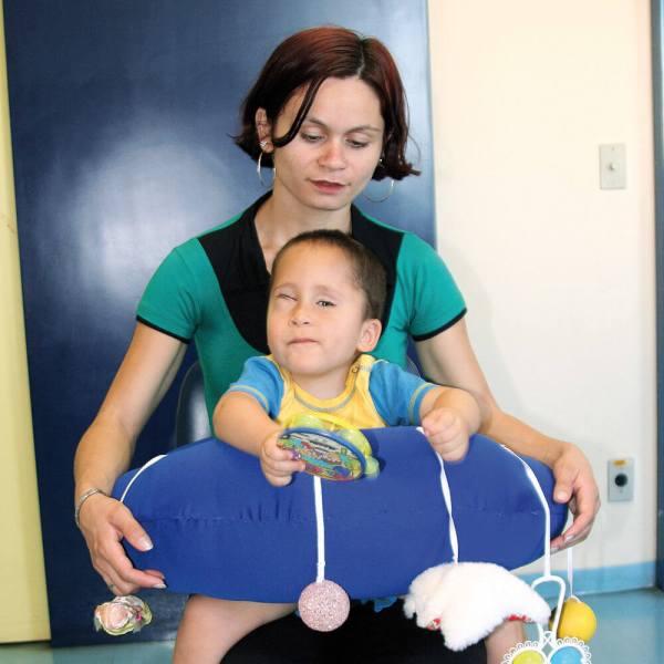 Menino de aproximadamente 2 anos, posicionado dentro do Brinque Baby. Com a mão direita, explora pandeiro, que está preso ao elástico. Atrás dele, a mãe observa.