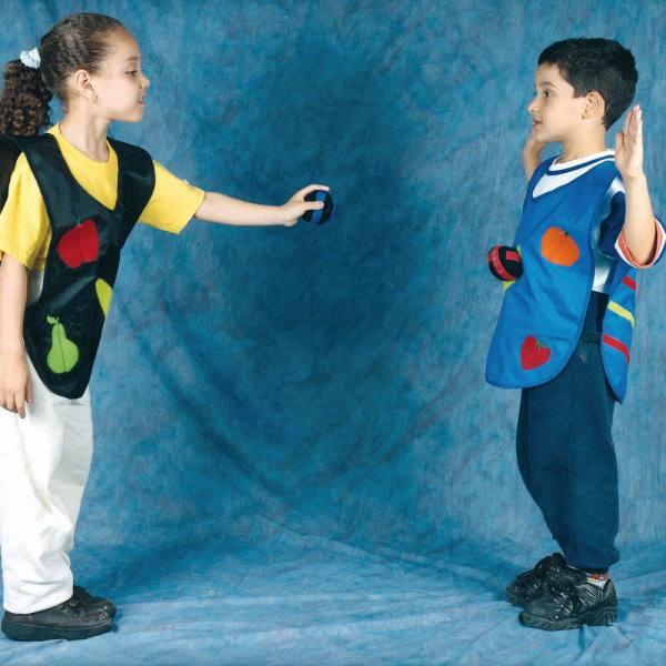 Uma menina e um menino de aproximadamente 6 anos, em pé, um em frente ao outro. Ambos com os coletes Cole Ball. Ela, à esquerda, cabelos escuros, cacheados e presos atrás da cabeça, está com o braço esquerdo estendido e na mão, uma fruta com velcro. Ele, à direita, cabelos escuros e curtos, está com as mãos para cima.