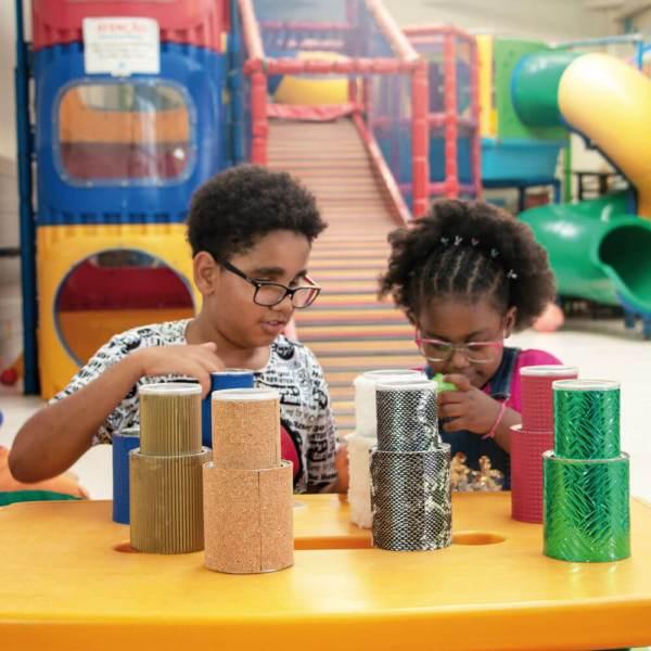 Menina e menino de aproximadamente 4 anos, sentados lado a lado, em frente à uma mesa, onde estão os potes do Encaixotando. Ele, cabelos escuros, cacheados e óculos, tem nas mãos dois potes azuis e ela, cabelos escuros, cacheados e óculos, dois potes brancos.