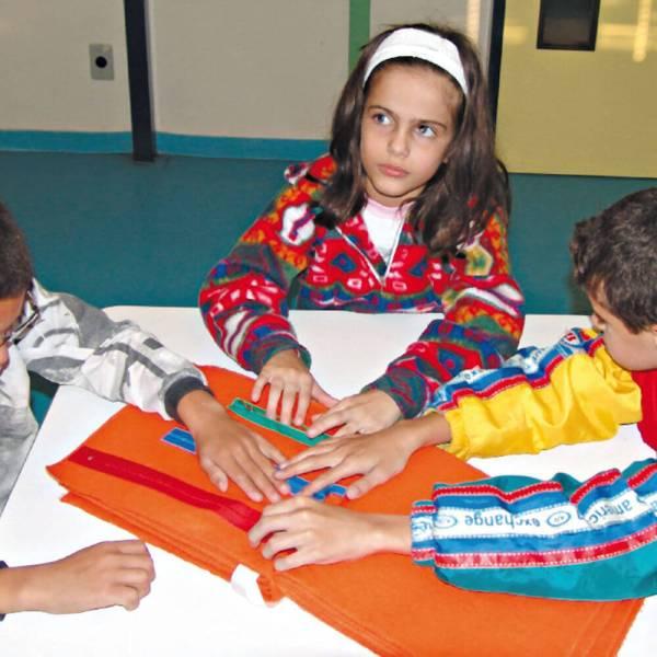 Menina e menino de aproximadamente 7 anos, sentados em frente à uma mesa branca. Em cima da mesa, o Livro das Grandezas. Com as mãos, tocam os zíperes de tamanhos e cores diferentes.