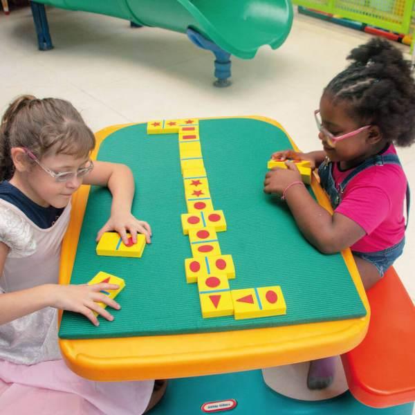 Duas meninas sentadas frente à frente e entre elas, o tabuleiro do Domine Formas. Ambas têm nas mãos, peças do jogo.