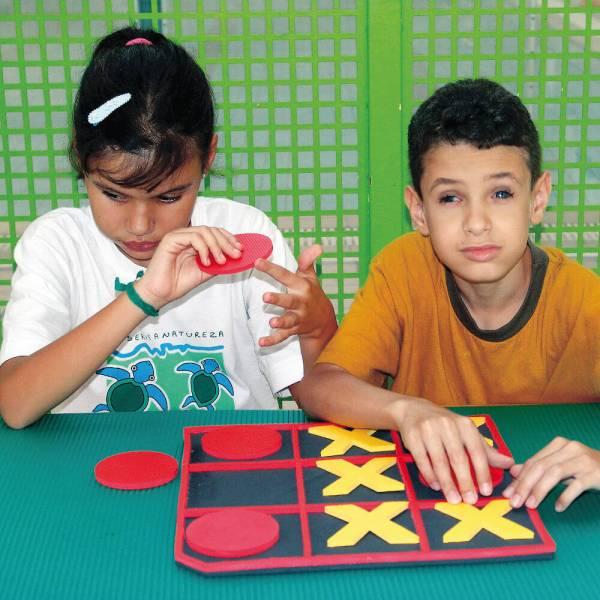 Uma menina e um menino, sentados lado a lado, em frente ao tabuleiro de Jogo da Velha. Ela segura um círculo vermelho e ele, toca o X no tabuleiro.