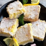 Gluten-Free Tart Lemon Bars on a plate with lemon slices and sprigs of mint