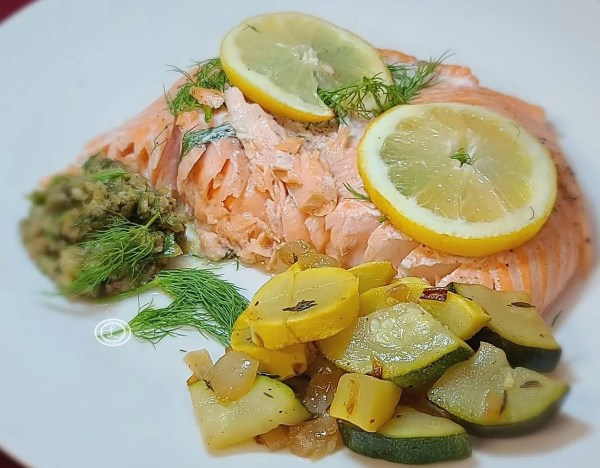 Salmon on a plate with Caper Dill Sauce and veggies.