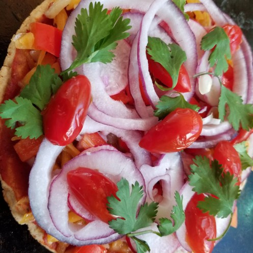 Pizza with cheese, ham, red peppers, red onions, grape tomatoes, and cilantro