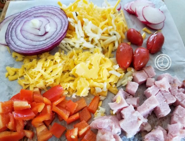 Red onion, red bell peppers, ham, cheddar cheese, tomatoes and radishes