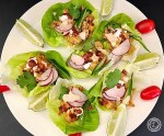 Chicken Taco Lettuce Wraps on a platter with lime and cherry tomatoes to decorate.